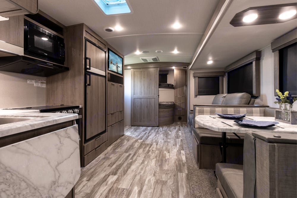 large living/kitchen area with a bunk area in the back. Grand Design Imagine 2910BH 2021