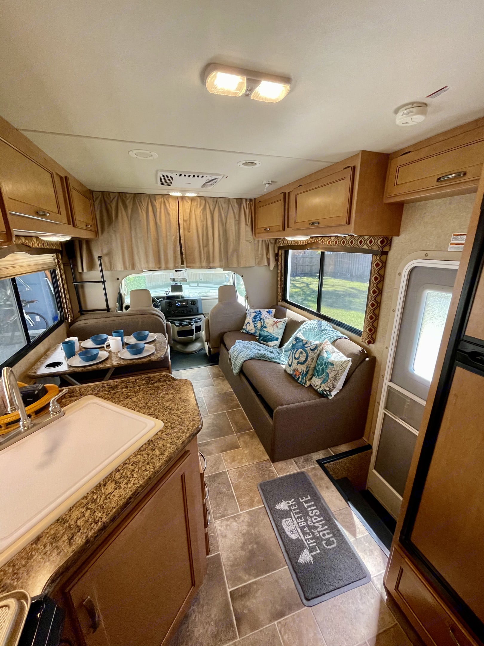 Plenty of room to relax or play games inside.  The curtain provides privacy for the queen bunk over the cab. . Thor Motor Coach Chateau 2016