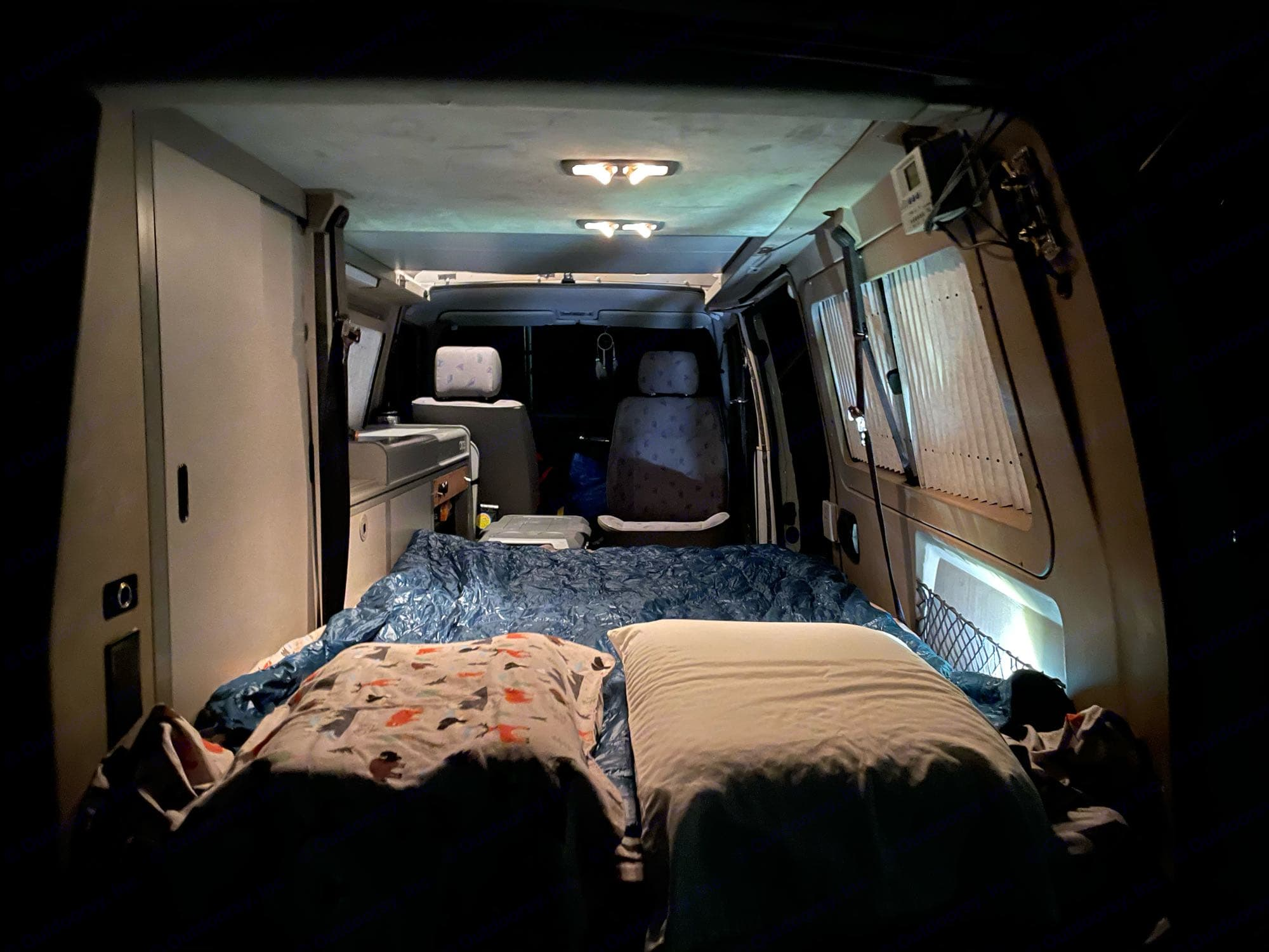 The back seat is folded flat and the topper mattress is laid out for sleeping for two. Bring your own blanket or sleeping bag.. Volkswagen Eurovan Camper 1997