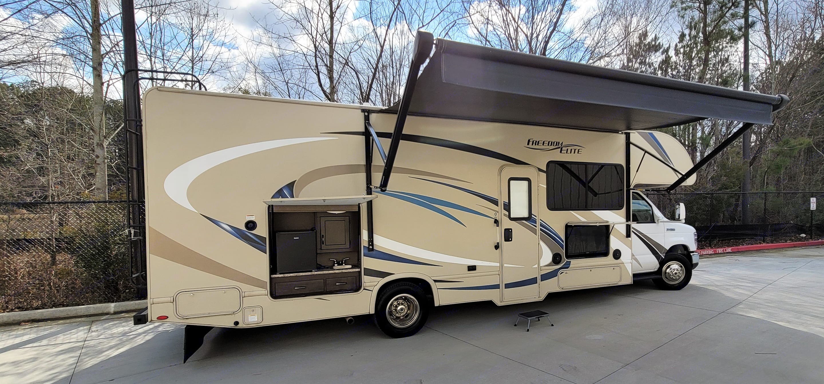 outside kitchen sink , refrigerator and table. Thor Motor Coach Freedom Elite 2018