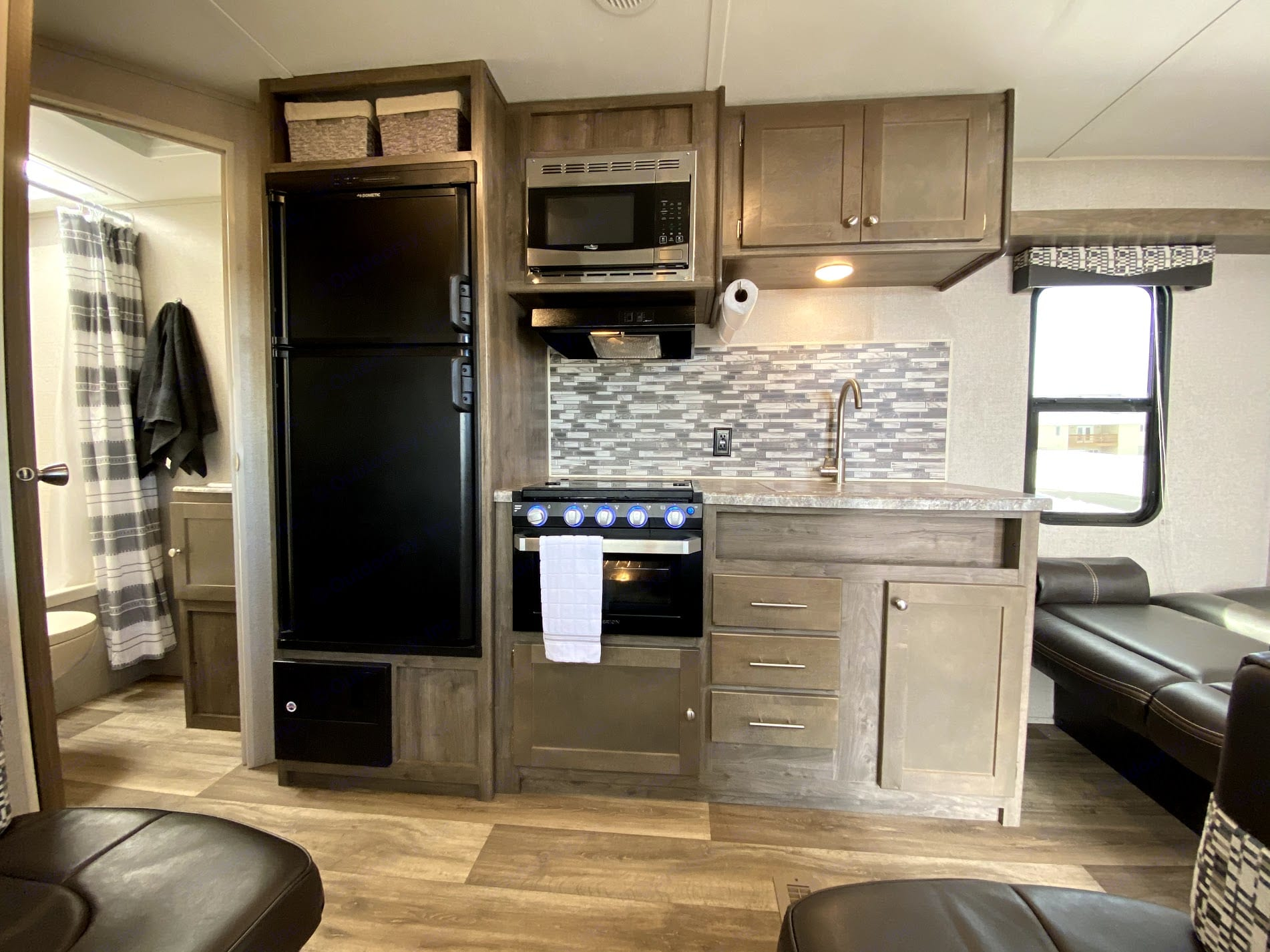 The kitchen is equipped with a sink, stove/oven, microwave and a fridge/freezer. . Dutchmen Aspen Trail 2019