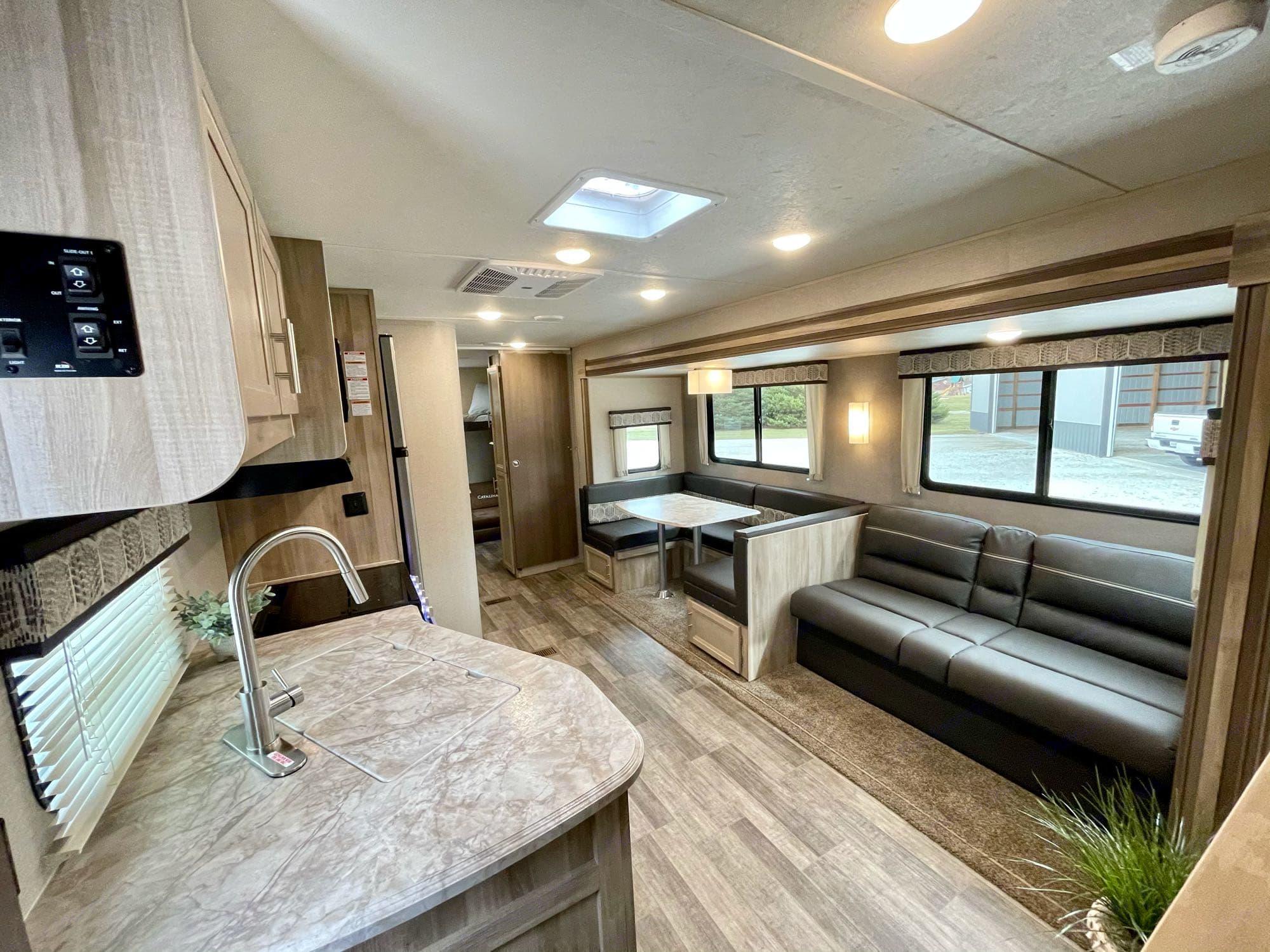 living area/kitchen. u-shaped dinette, gas stove, oven, microwave. Coachmen Catalina 293QBCK 2021