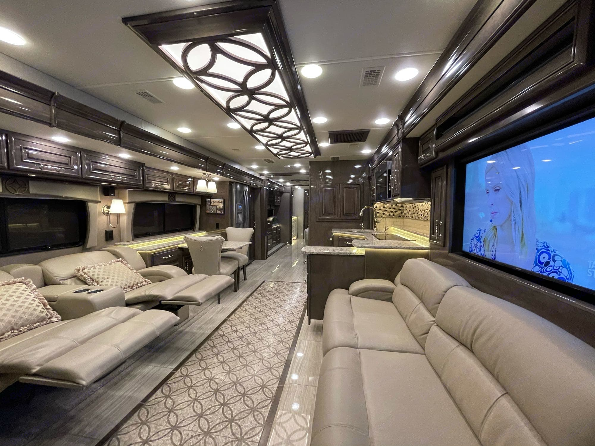 """Living room area with entertainment seating and """"televator"""" that stows away during travel.. Entegra Coach Cornerstone 2019"""