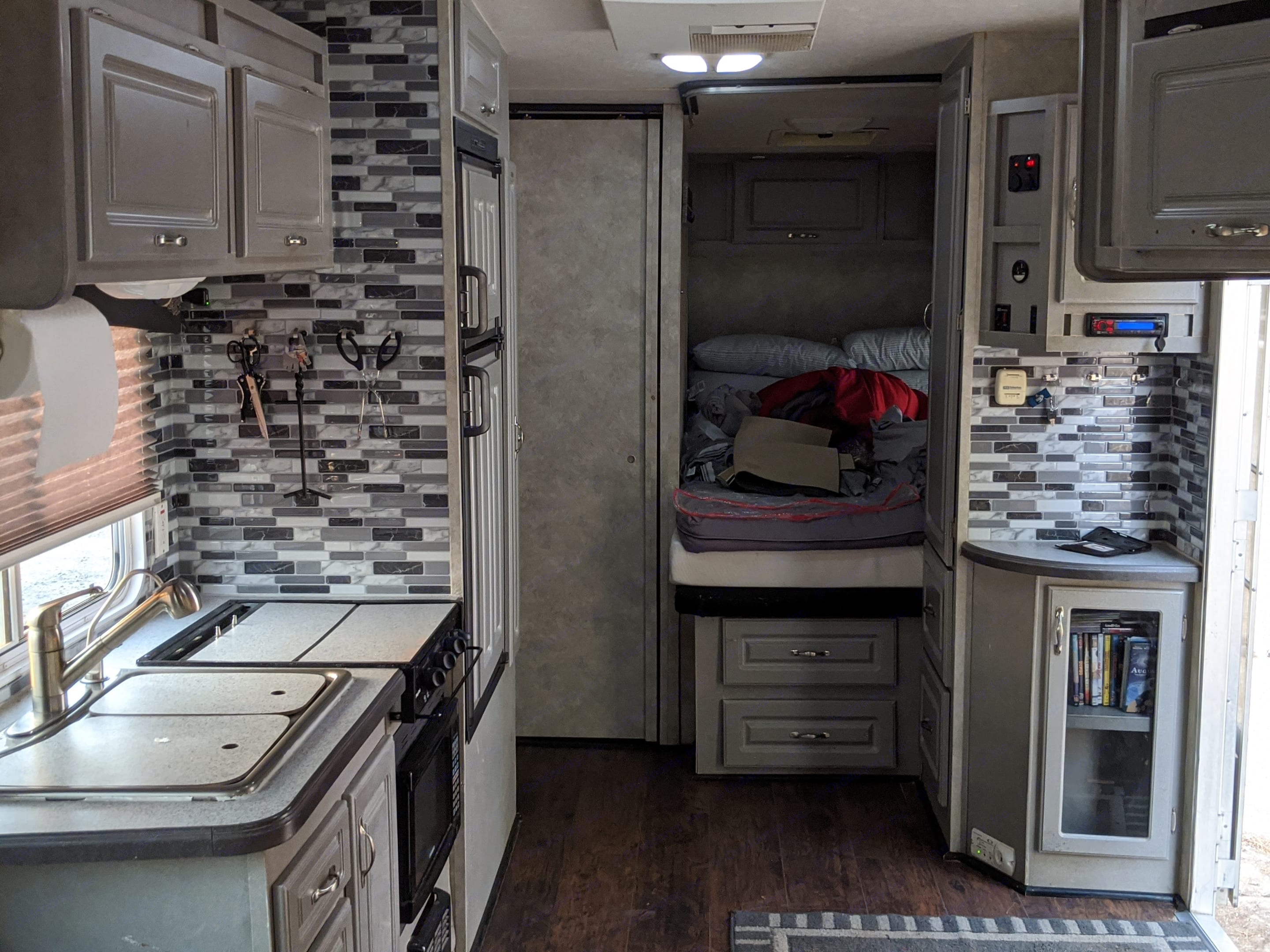 Front end of the interior of the trailer.  Full bed, door to restroom, and kitchen cook top and sink.. Weekend Warrior Super Lite SS-2500 2009