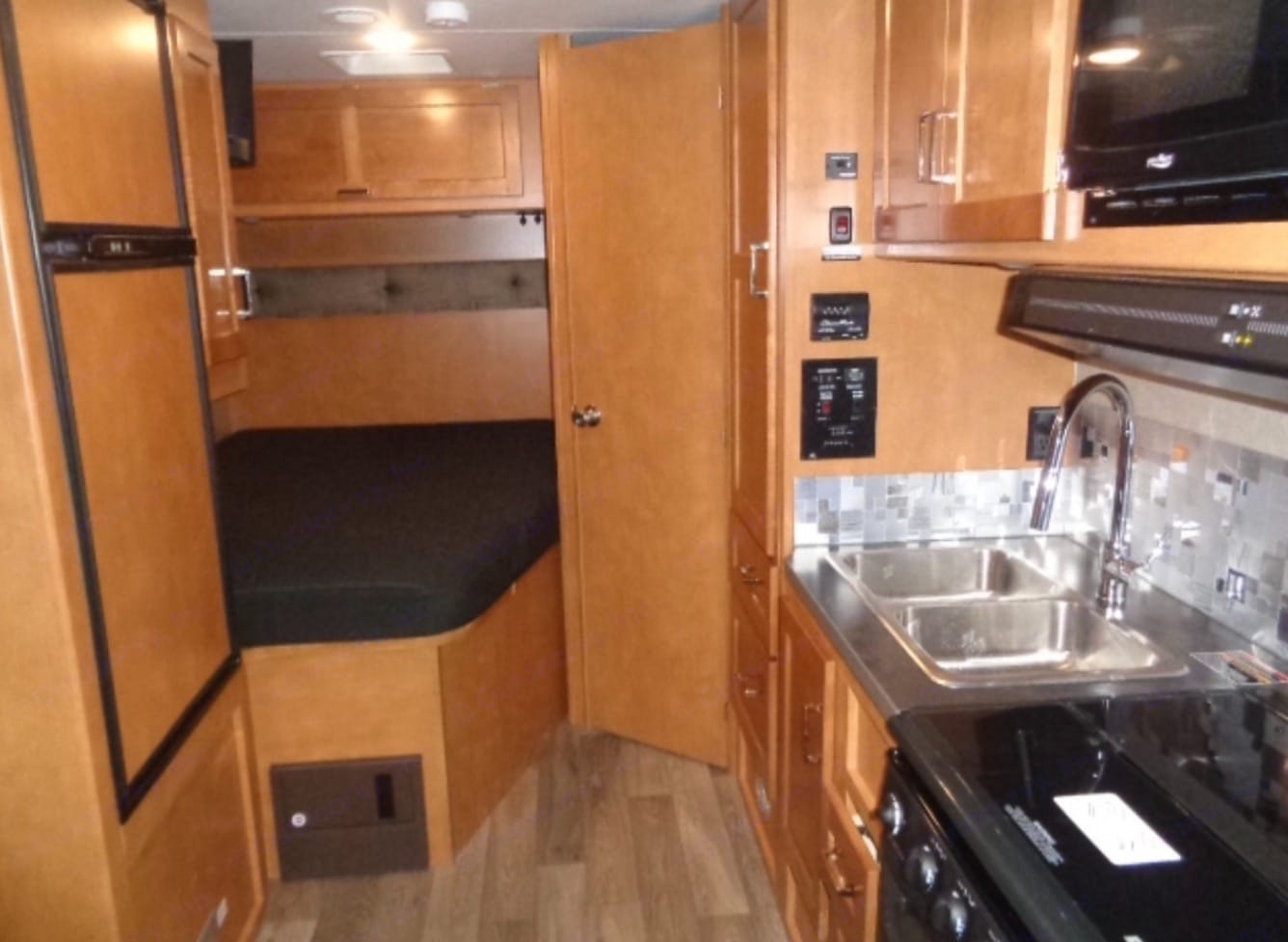 Queen bed, side view kitchenette with double sink with pull down sink/sprayer and stove/oven.. Winnebago Minnie Winnie 2019