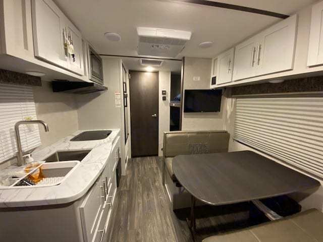 Kitchen and dining area/full size bed. Keystone Bullet 2021
