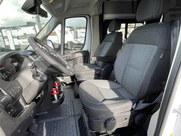 View of driver and passenger seats, which are comfortable. Visibility is great and backing up no sweat with the in dash back-up camera. . Winnebago Solis 2020