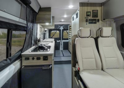 View aft from the front. Kitchen is on left, with fridge below. Bathroom on the right and at the end is where the queen sized bed is presently stowed.. Winnebago Solis 2020