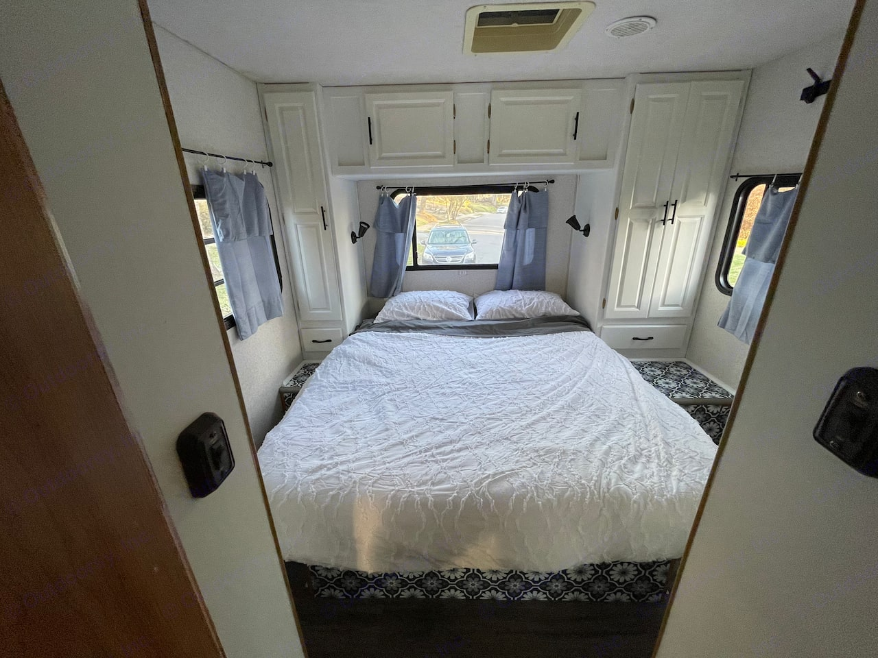 The large bedroom at the back of the RV, boasting a RV queen bed with memory foam mattress and tons of storage.. Coachmen Santara 2001