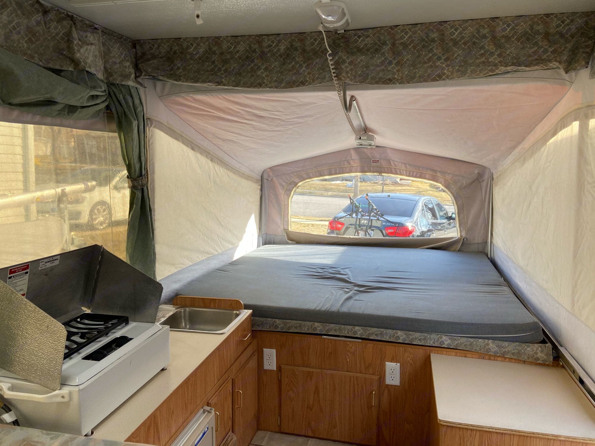 This is a pic of the queen popout bed and you can see the cooktop there and the sink as well. . Jayco Eagle 2003