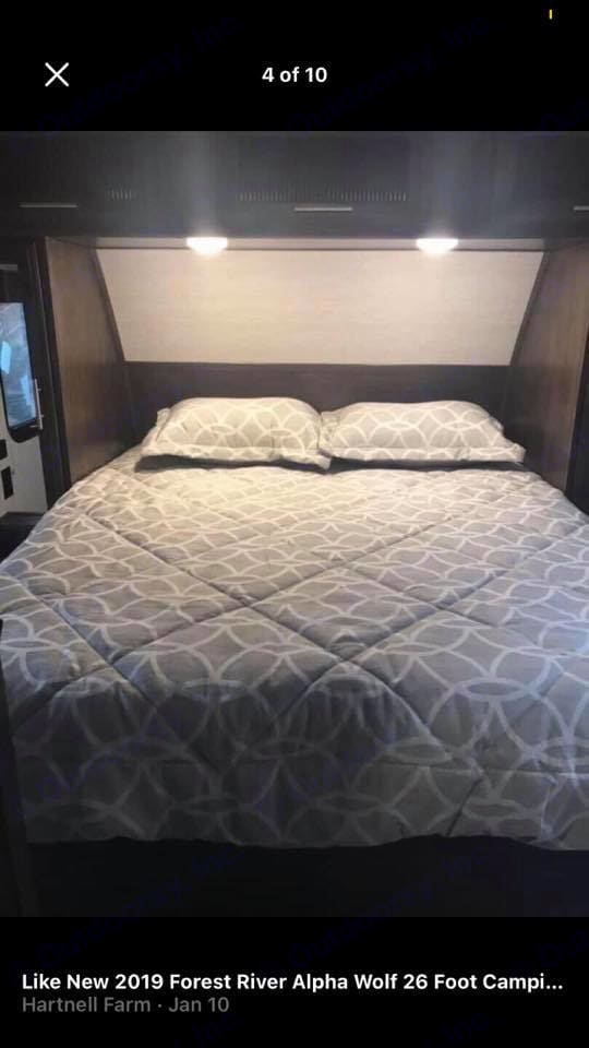 Queen Bed with lights above for reading with storage on each side to put your clothes in while you are camping, . Forest River Cherokee 2019