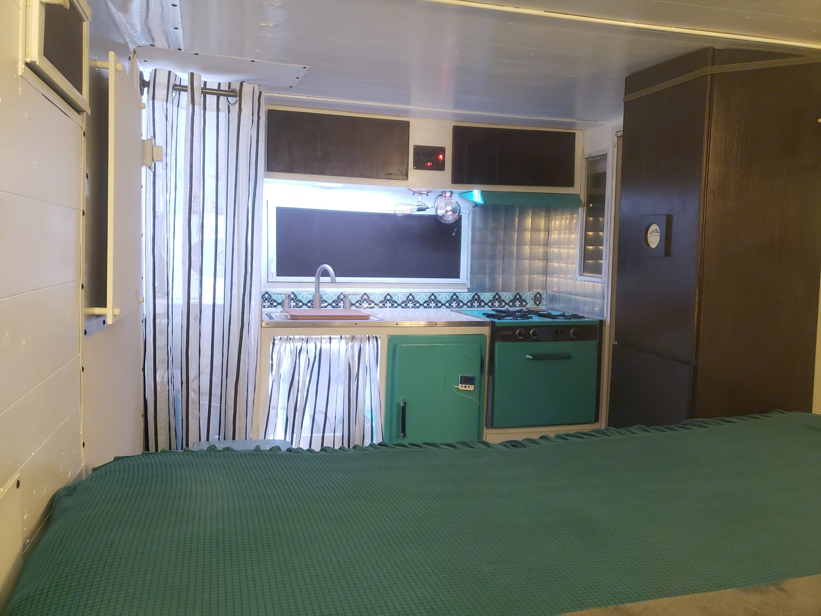 A view of the interior with the bed folded out.. Aristocrat Lo-Liner 1963