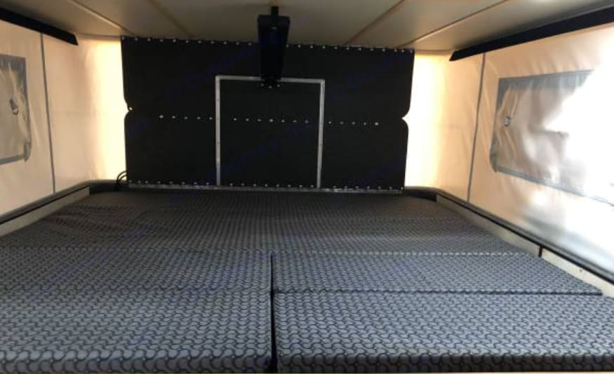 """Queen-sized """"main"""" sleeping area above truck cab.. Four Wheel Campers Fleet 2016"""