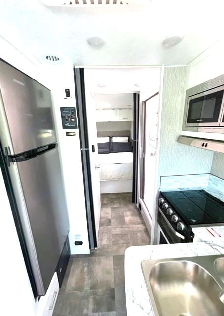 Front to back View of kitchen area. Leading into hallway towards master bedroom with a full shower on right and private restroom on the left.. Coachmen Pursuit 2021