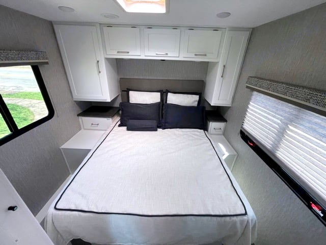 Beautiful farmhouse style interior. Really showcased in this photo of the Master bedroom. Super comfy and spacious bed.. Coachmen Pursuit 2021