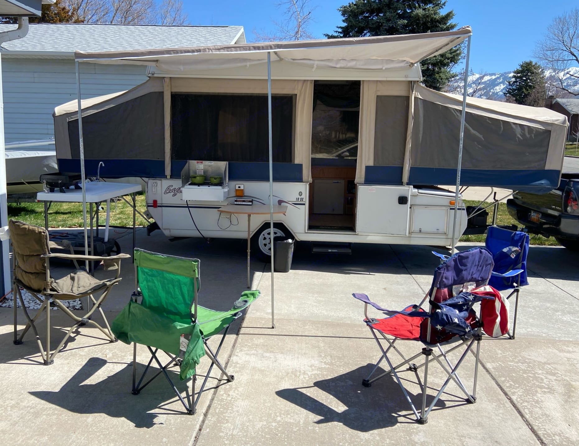 In this photo you can see the full outdoor kitchen setup. The awning and camp chairs. The outdoor cooktop. Coleman grill. Outdoor sink prep table. . Jayco Eagle 2003