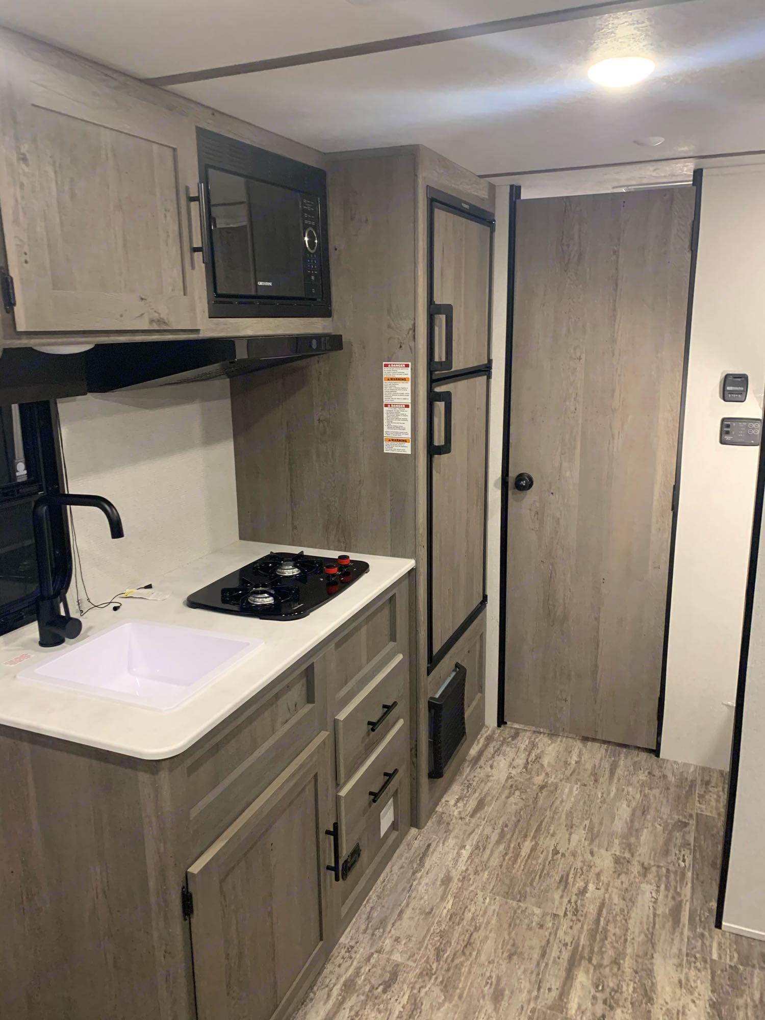 kitchen with stove top, microwave, huge fridge/freezer, and sink. Keystone Springdale 2021