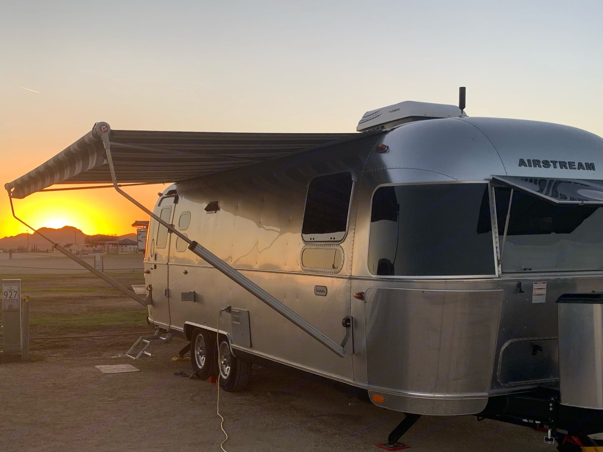Sun setting over the lake behind our rig. The awning is out because we enjoyed drinks in the shade earlier.. Airstream Globetrotter 2019