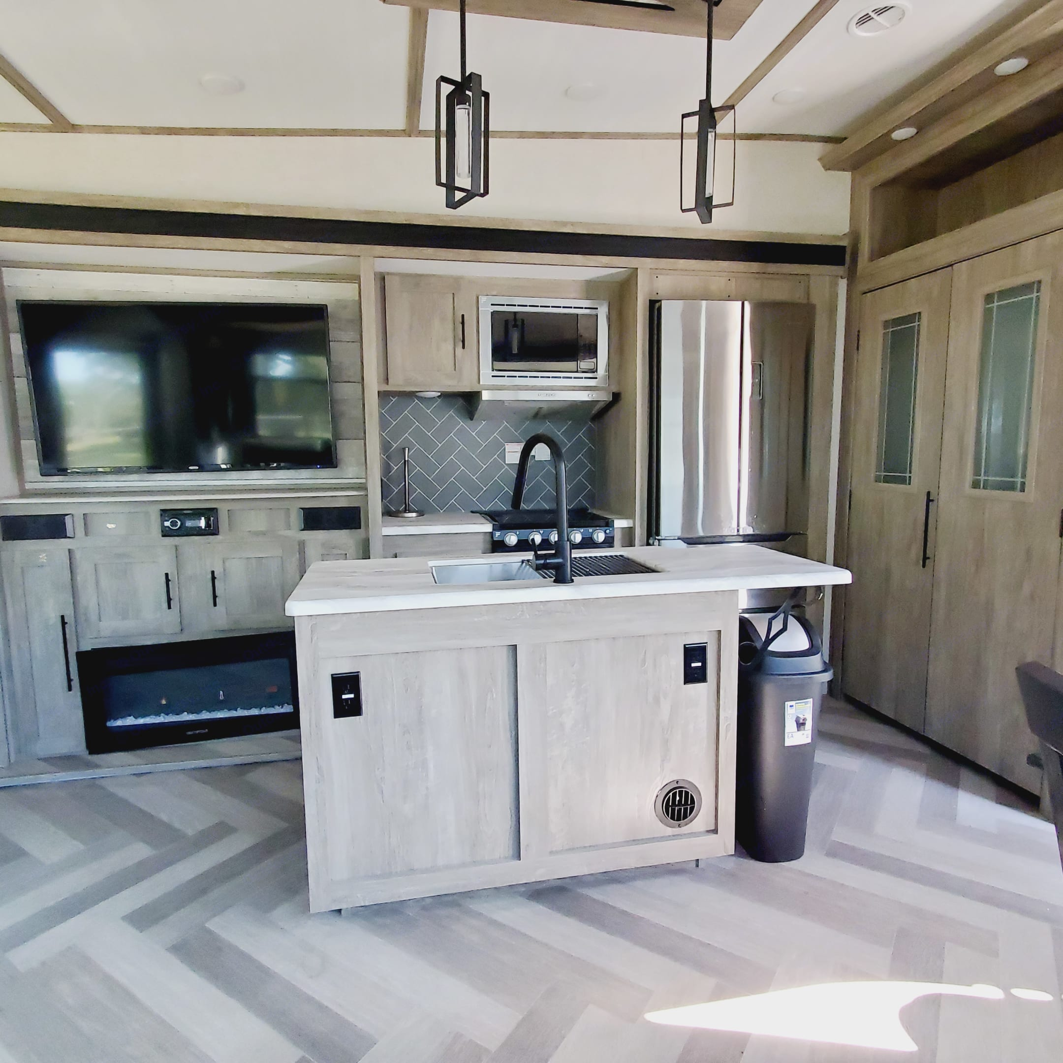 Kitchen with stainless steel appliances, large flat screen tv and electric fireplace.. Forest River Heritage Glen 2020