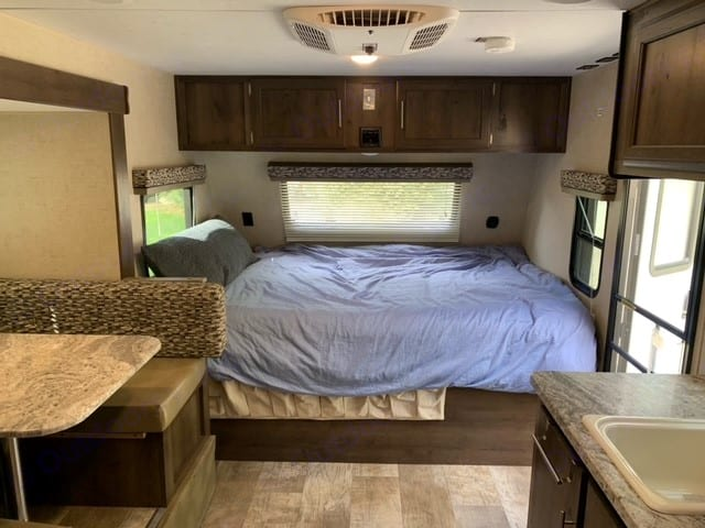 Queen bed in front, many windows, storage cabinets above; shoe storage below, a/c on ceiling. K-Z Manufacturing Escape 2018