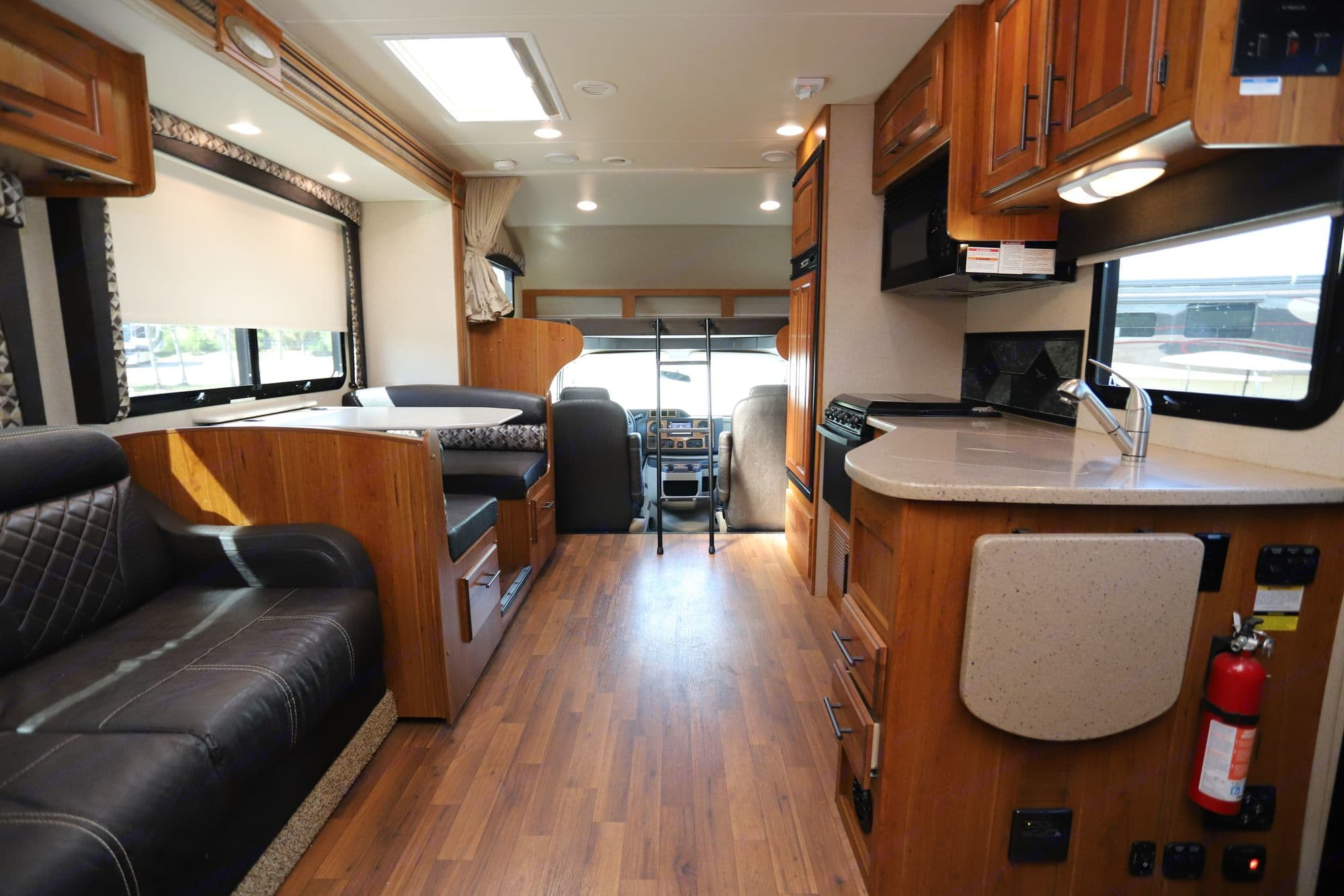 View of interior living space from just inside entry door.  Plenty of seating, spacious kitchen, and kids love the bunk over the cab!. Jayco Greyhawk 2017
