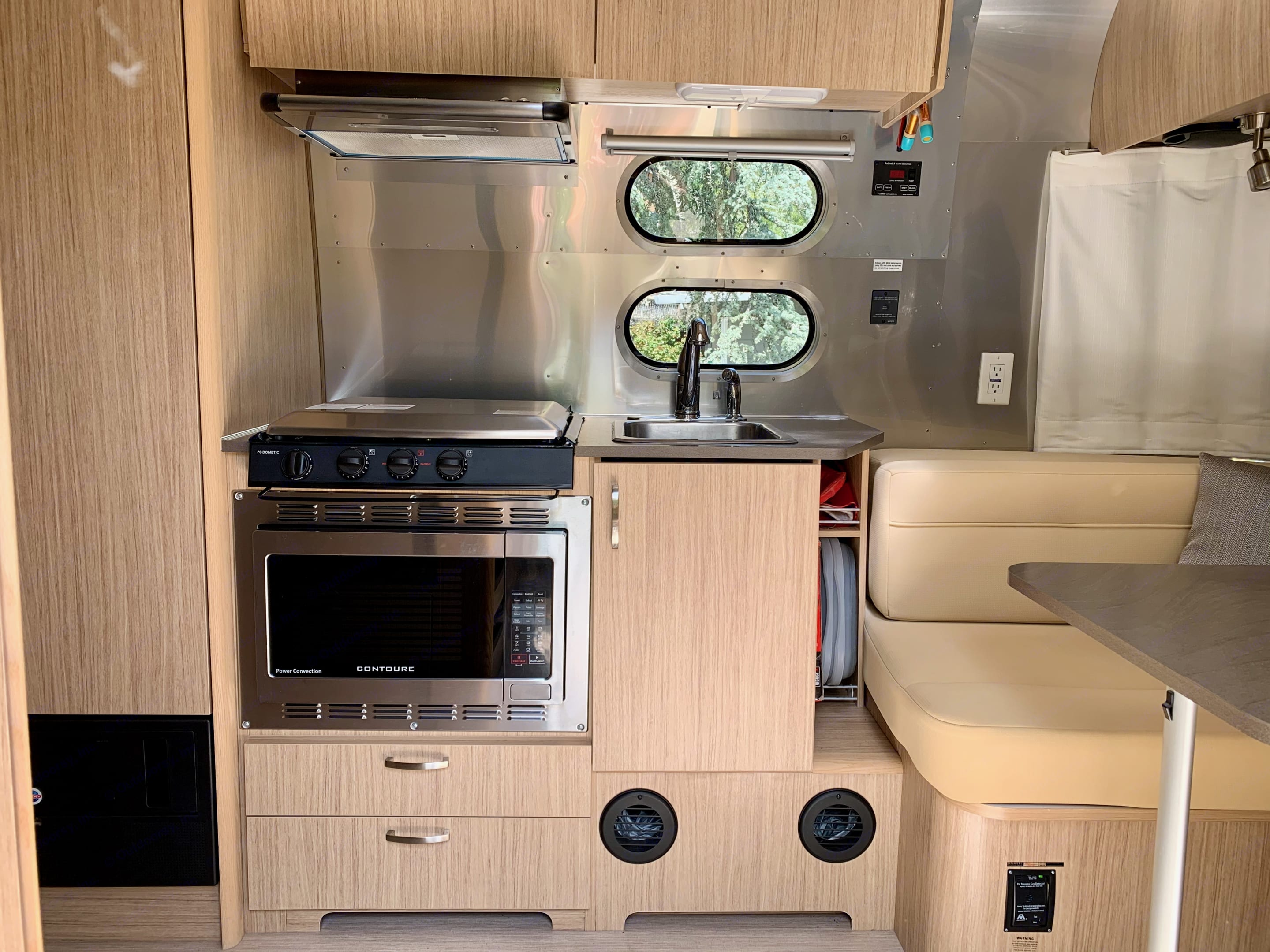 Kitchen with gas stove, sink and microwave/oven combo. Airstream Flying Cloud 2019