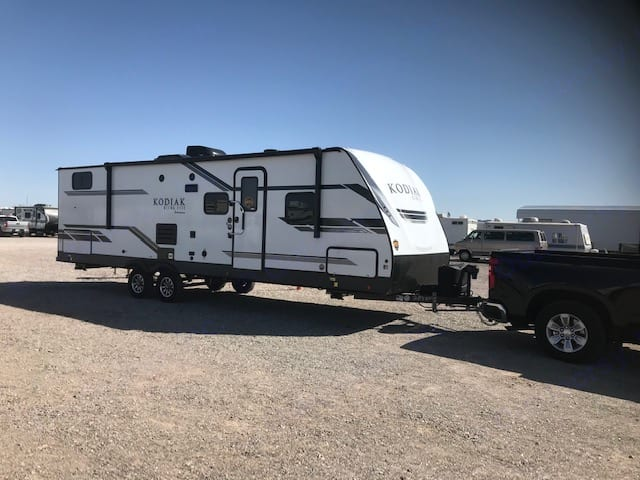 The travel trailer has a small outdoor kitchen with a fridge and a burner. Located at the back of the trailer. Big awning for shade and outdoor shower. Dutchmen Kodiak 2021