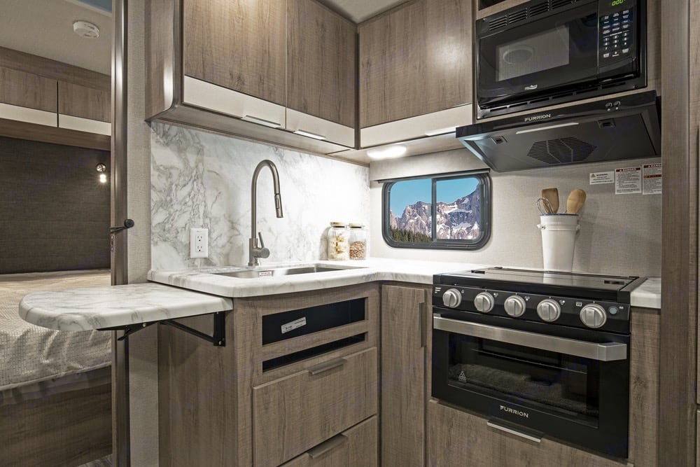 Double wide stainless sink w/ telescoping spray wand, fold up counter extension and plenty of storage. Oven & 3 burner stove, with microwave up above. Grand Design Imagine 2400BH 2022