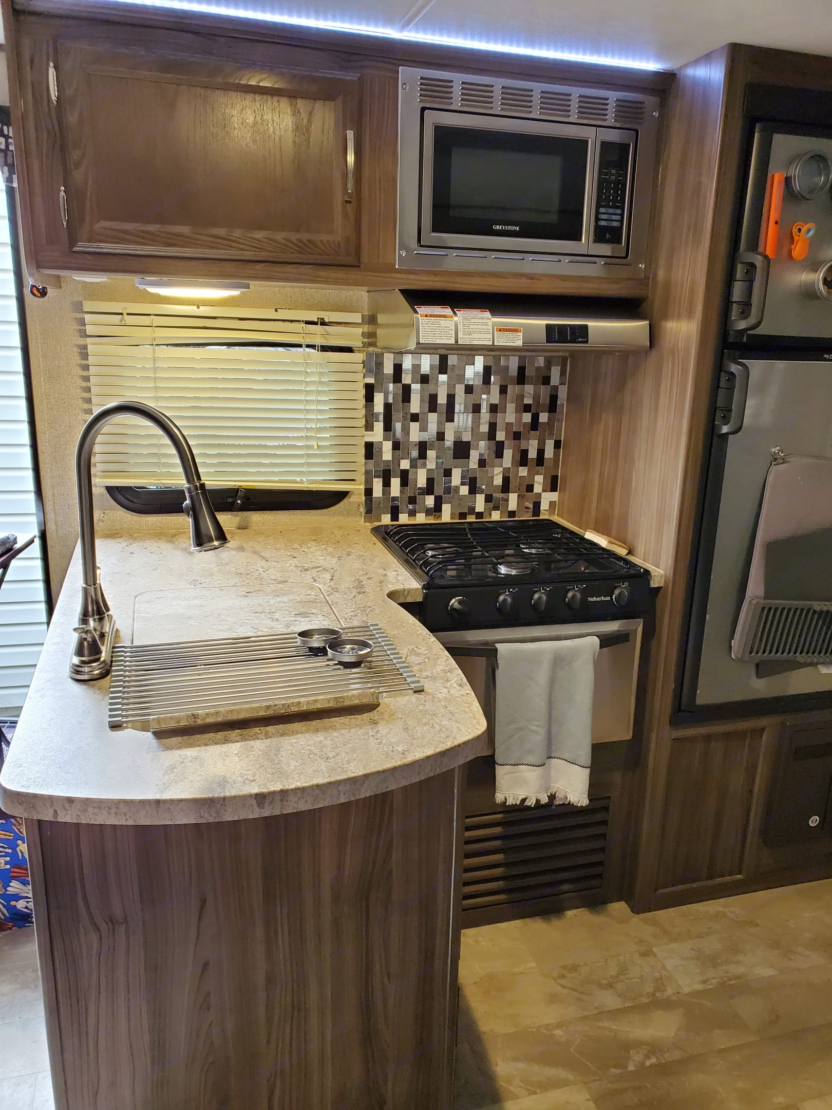 Microwave, 3 burner gas stove, gas oven, dual-sided sink, and loads of cookware!. Coachmen Apex 2018