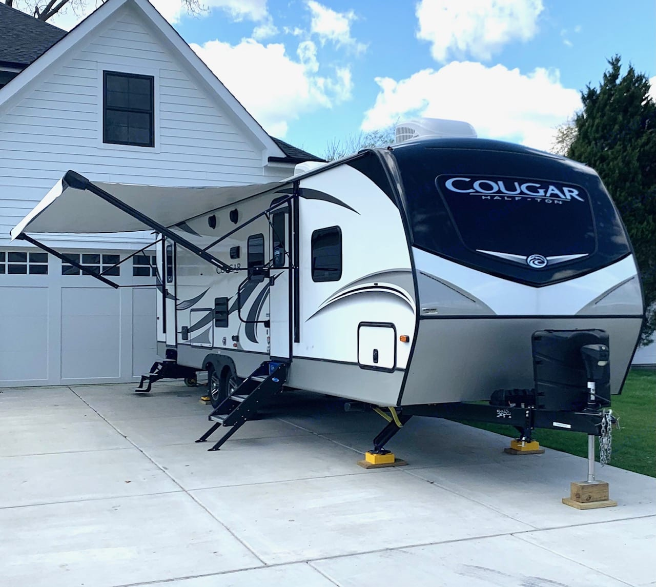 Electronic hitch jack and four point auto leveling stabilizer jacks.  RV comes has two batteries and two propane tanks.. Keystone Cougar 2020