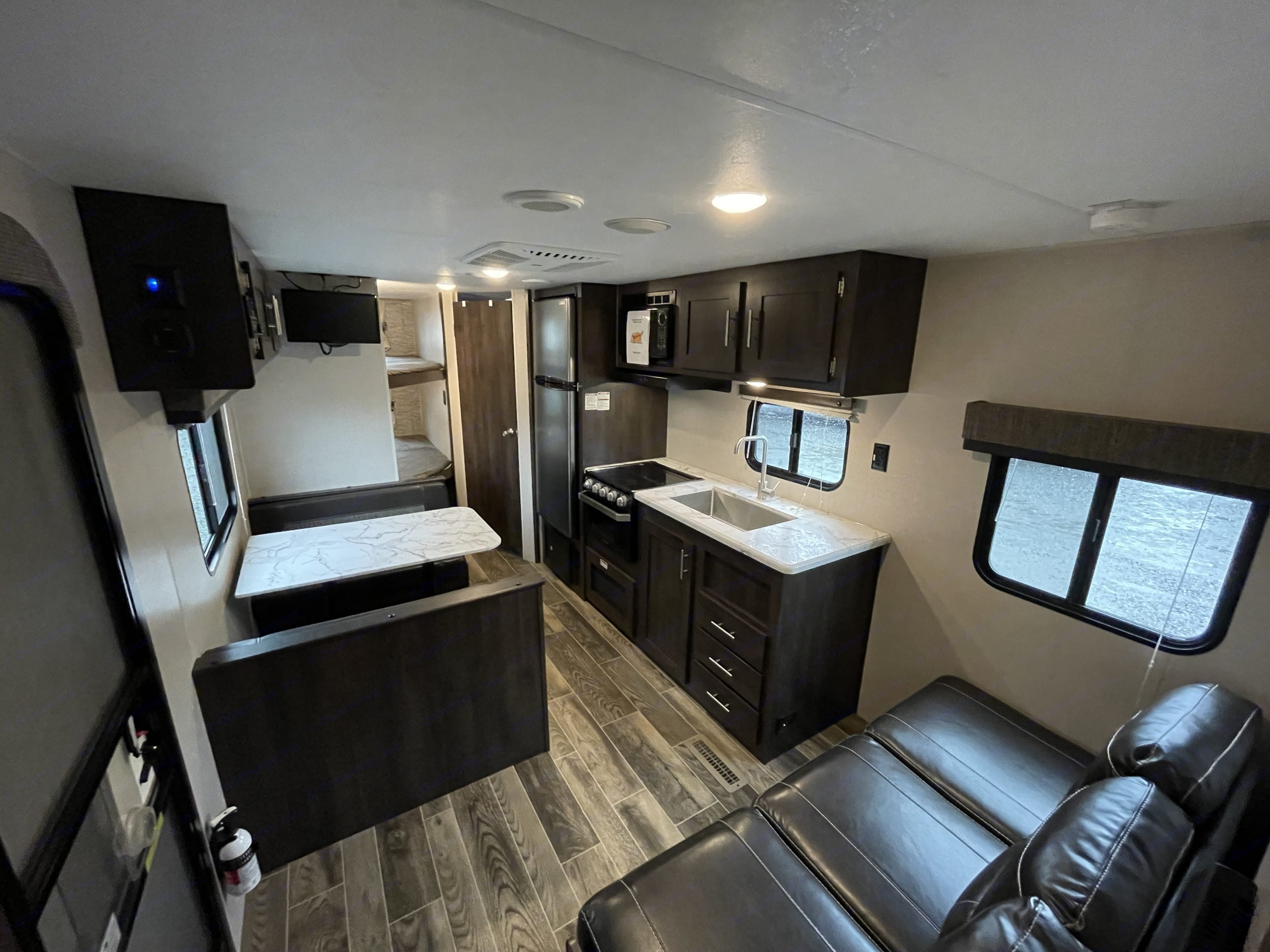 This is a picture from the view of the master bedroom door, overlooking the couch, tv, dining area, and full kitchen!. K-Z Manufacturing Sportsmen 2019