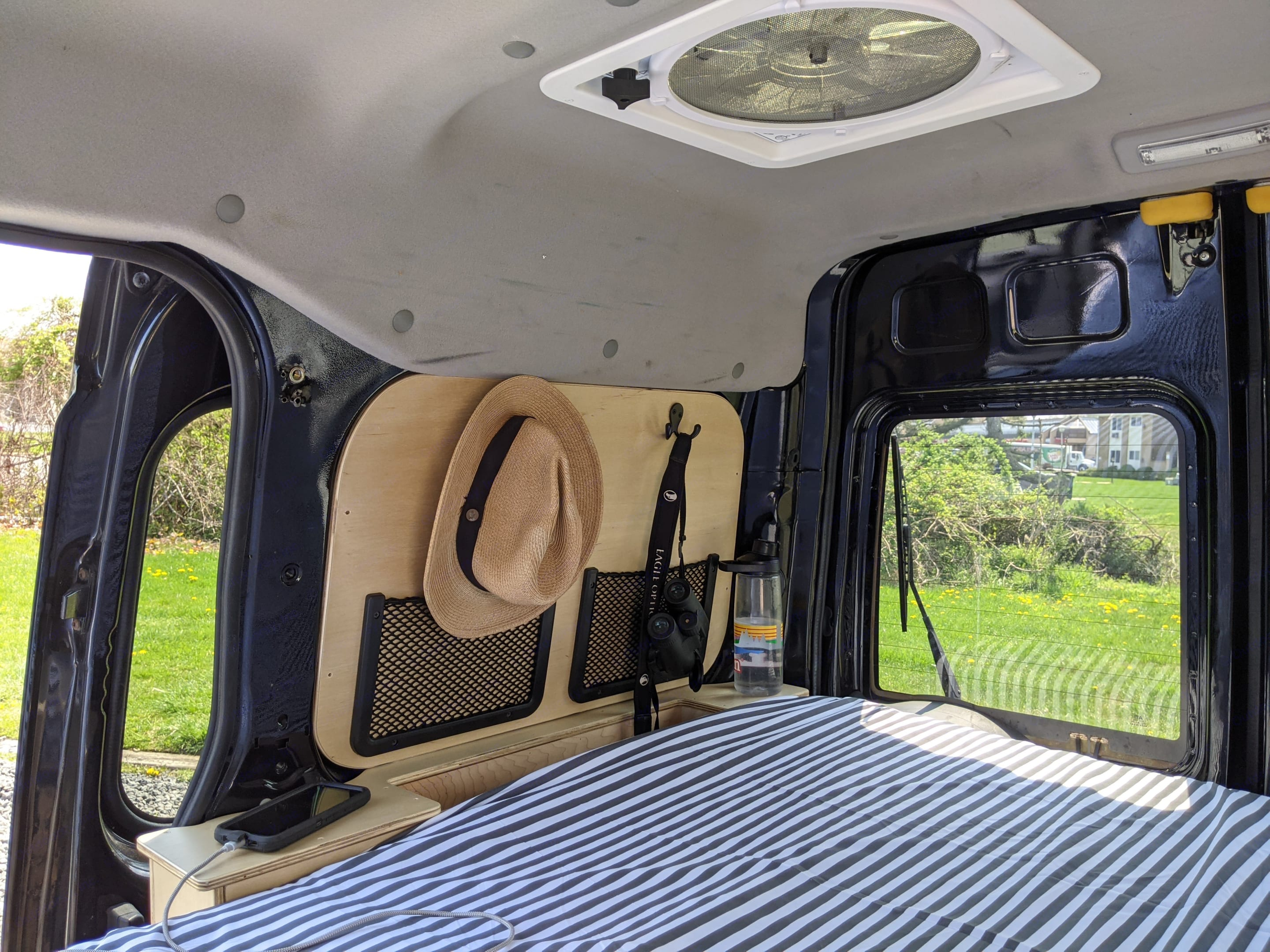 Dual bedside cubbie storage, ceiling vent fan and narrow queen sized bed. Ford Transit Connect 2012