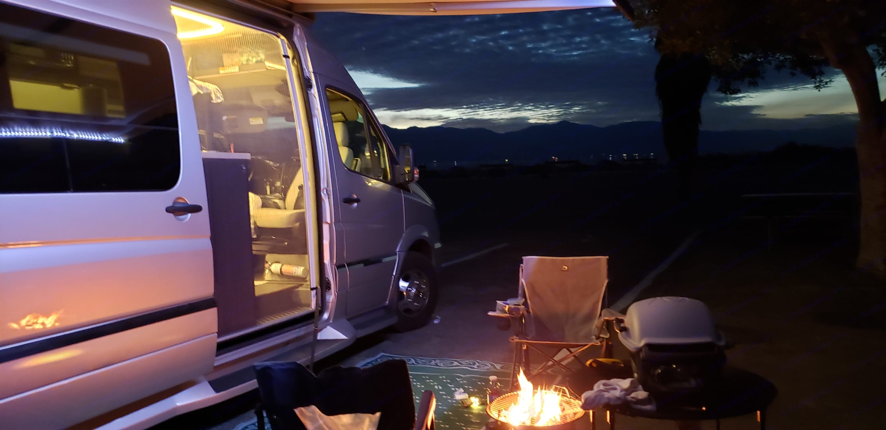 lit awning with propane fire pit, camping chairs and outdoor barbeque.. Winnebago Mercedes Sprinter 2018