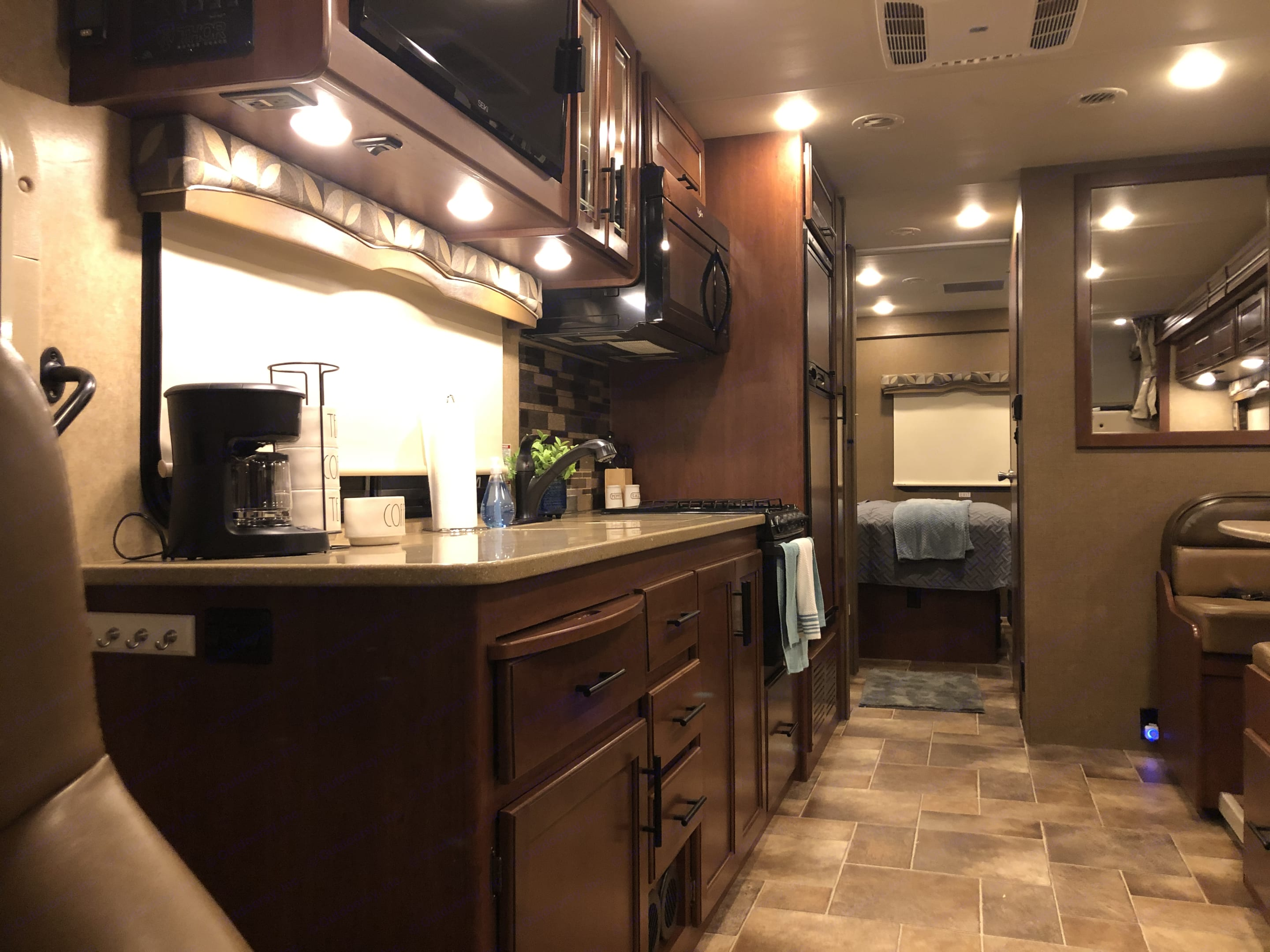 Looking back from the drivers side view you see the gorgeous interior. The kitchen to the left with sofa and dinette located on the right. . Thor Motor Coach Chateau 2017