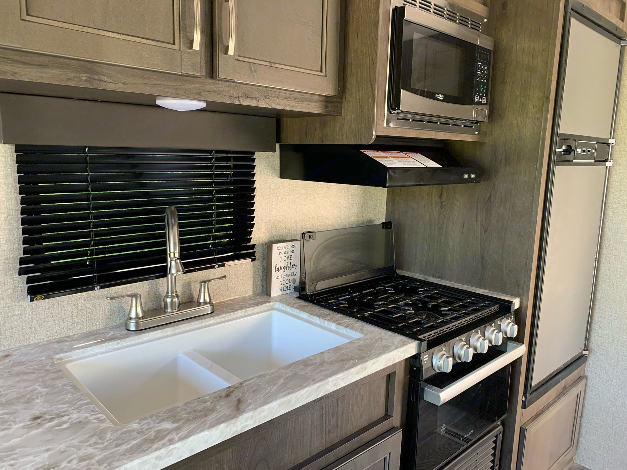 Double sink next to stovetop with oven underneath. Jayco Jay Flight 2021