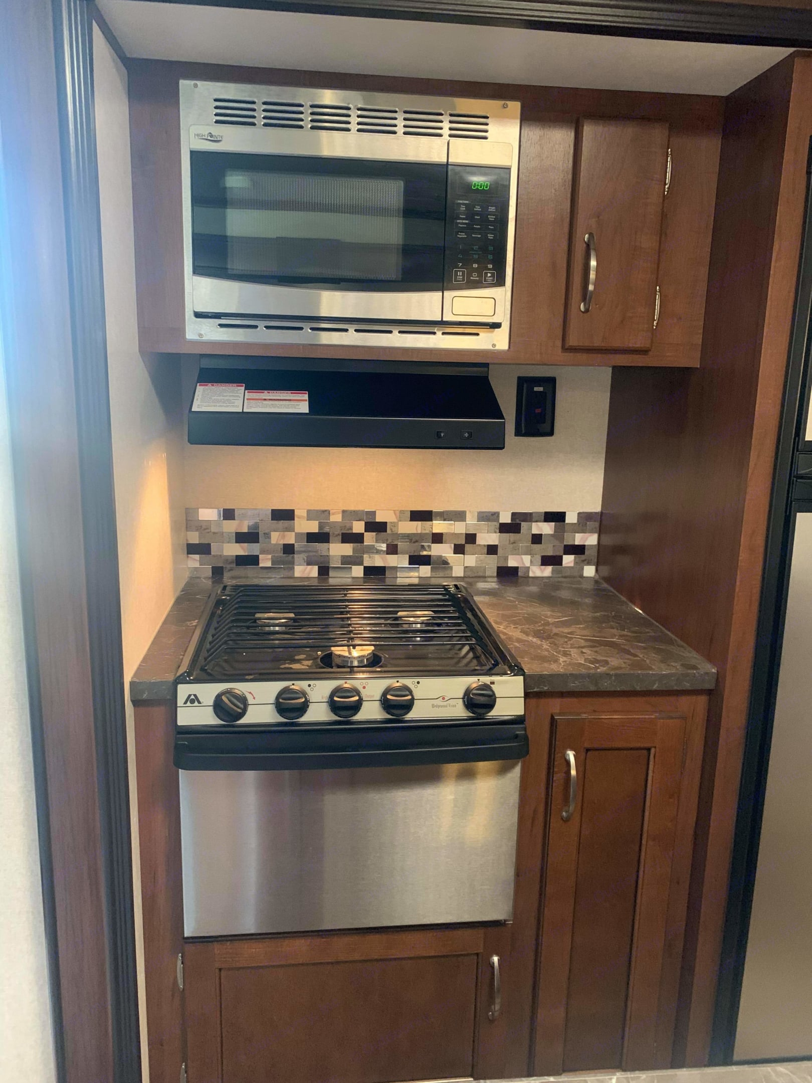 Indoor kitchen with stove and microwave, as well as range hood.. Jayco Jay Flight 2017