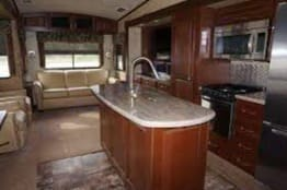 Interior dining room, kitchen and seating area.. Forest River Cedar Creek Fifth Wheel 2015