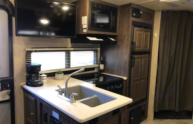 Open Kitchen concept with sink, oven, stovetop, microwave, fridge & freezer and flatscreen above. . Forest River Rockwood Mini Lite 2018