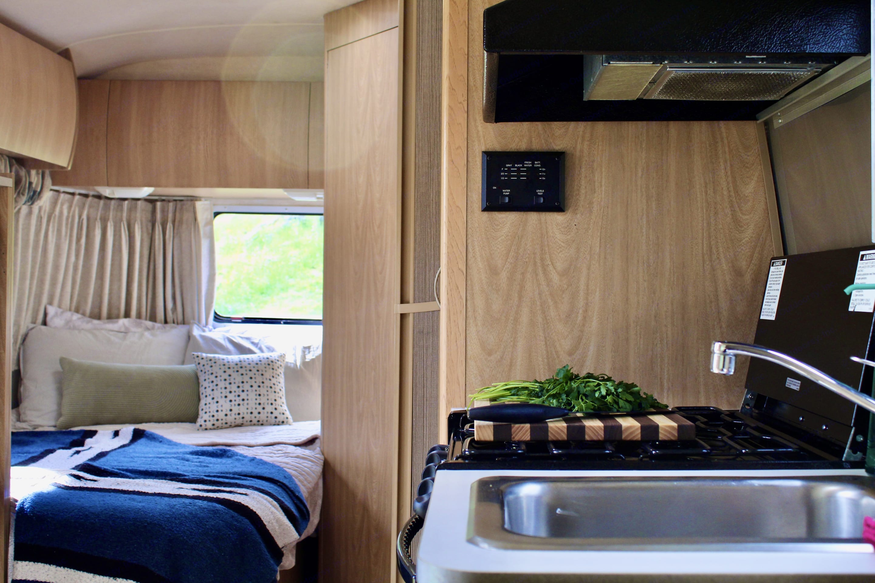 View of the kitchen, bed, and bathroom from the dining table. Airstream Safari Bambi 2003