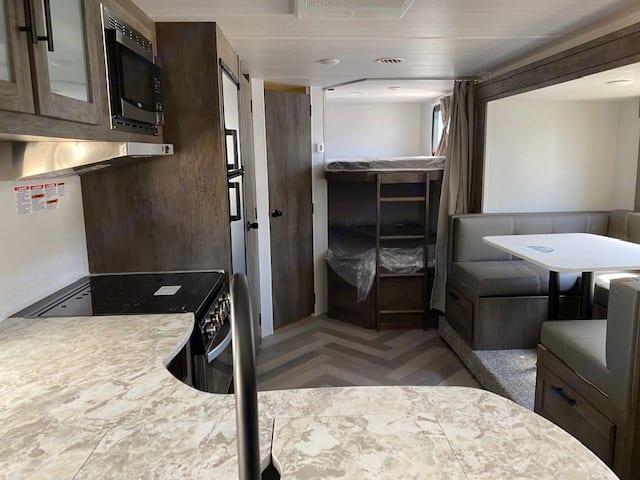 Kitchen area & bunk beds in back, restroom door next to beds.. Forest River Salem Cruise Lite 2021