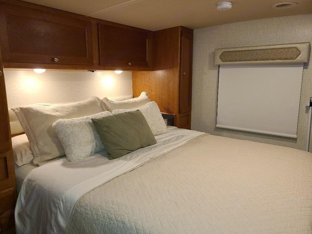 Main bedroom has queen bed, TV, lots of storage and sliding door for privacy. . Winnebago Sunstar VE 2017