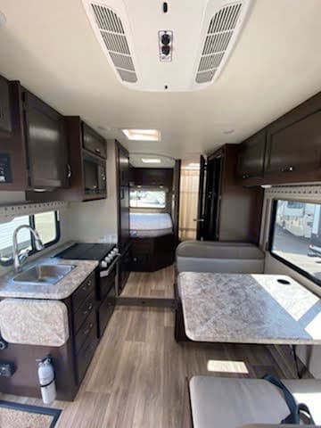 Full size bed, full bathroom, kitchen with fridge, oven, and microwave. Seating for 4.. Thor Motor Coach Four Winds 2020