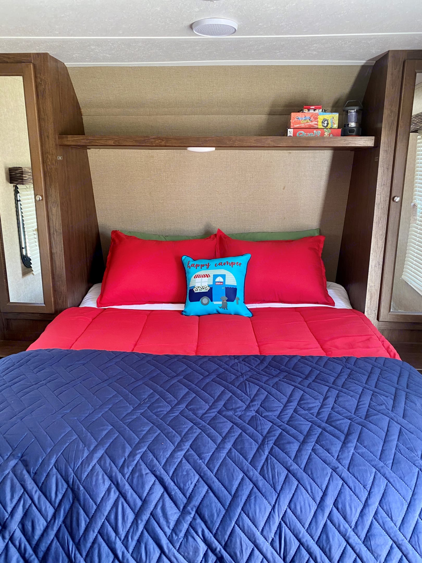 Queen bed with two standard pillows, body pillow and happy camper throw pillow.. Keystone Hideout 2017