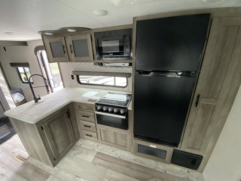 Microwave, 3 burner cooktop, stove, and refrigerator . K-Z Manufacturing Sportsmen 2021