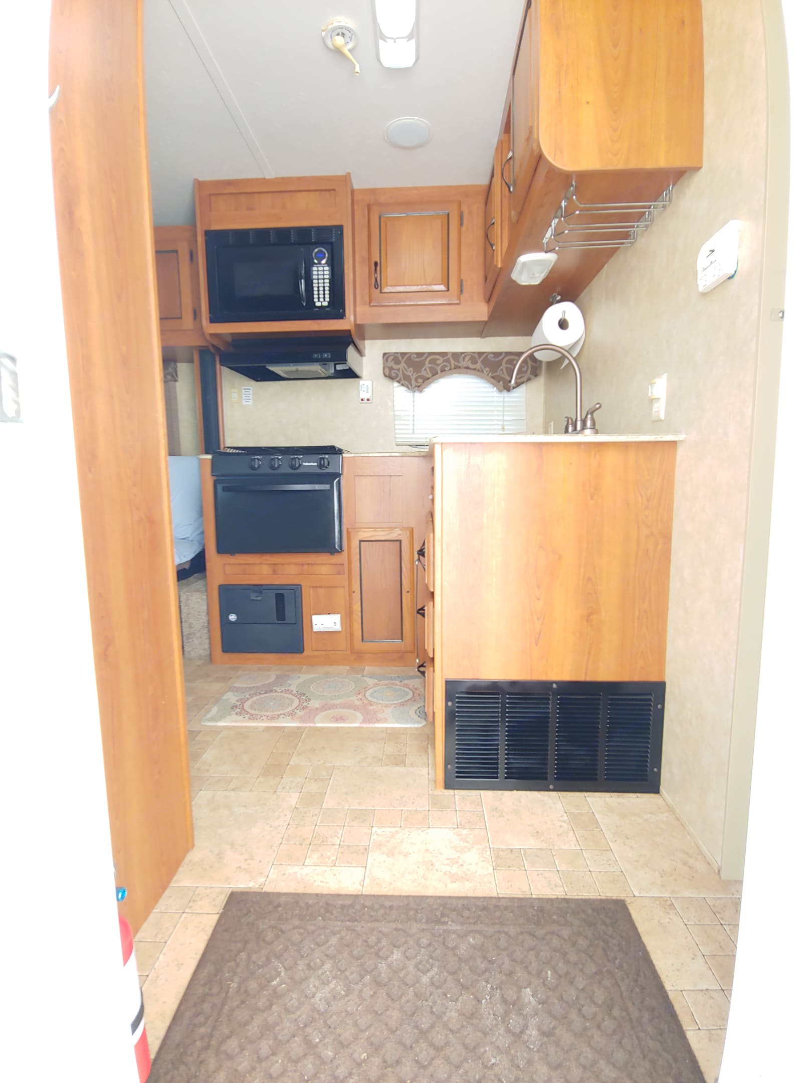 Kitchen from entrance. 3 burner stove, oven, microwave, double sink, and fridge with top freezer.. Coachmen Catalina 2011