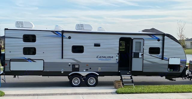 Exterior- passenger side awning and LED lights, steps that allow for any leveling situation. Forest River Catalina 2021