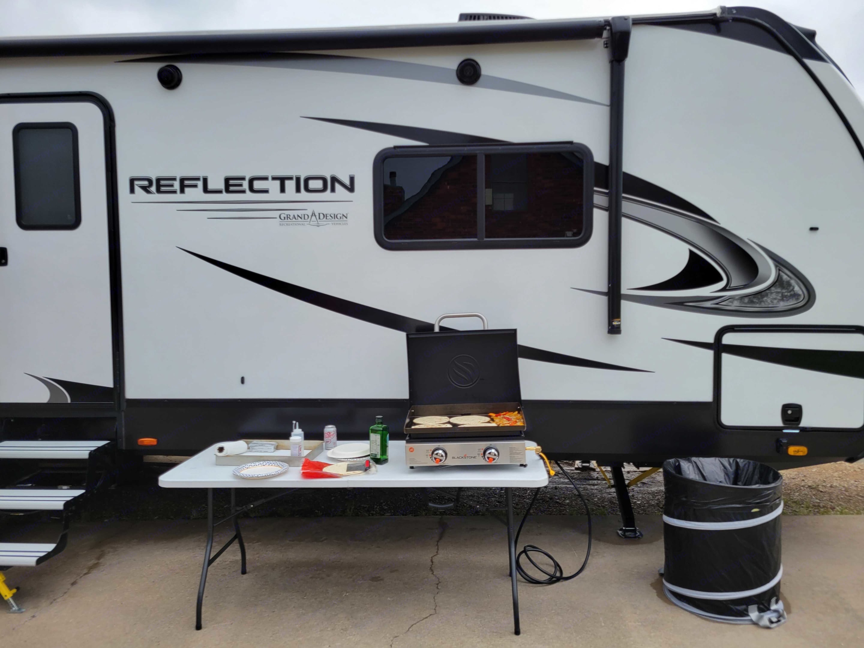 Outdoor cooking setup with griddle and folding table. Grand Design Reflection 2021