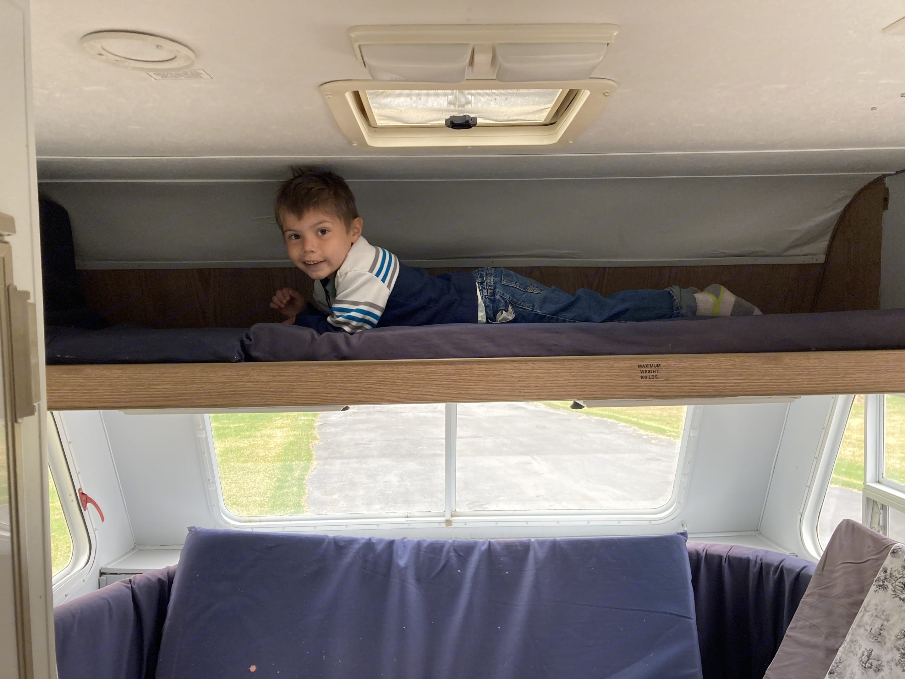 100 lb MAX! Very small bunk suitable for a SMALL child. My son it 5 and he loves it up there! . Aerolite Travel Trailer 1996