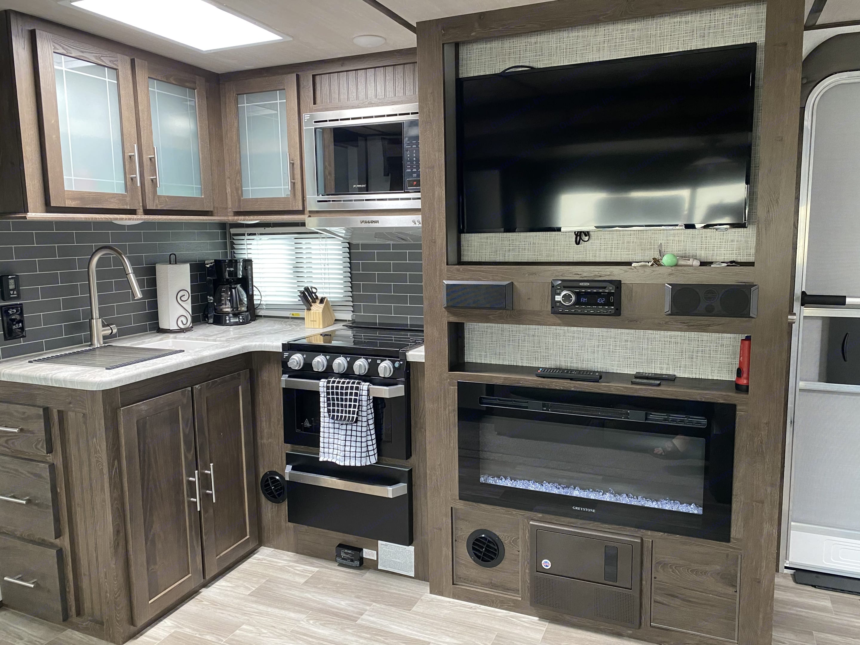 """Fully equipped kitchen with sink, stove, oven, microware.  Entertainment space includes 32"""" TV/DVD system w/ electric fireplace.. Forest River Salem Hemisphere 2020"""