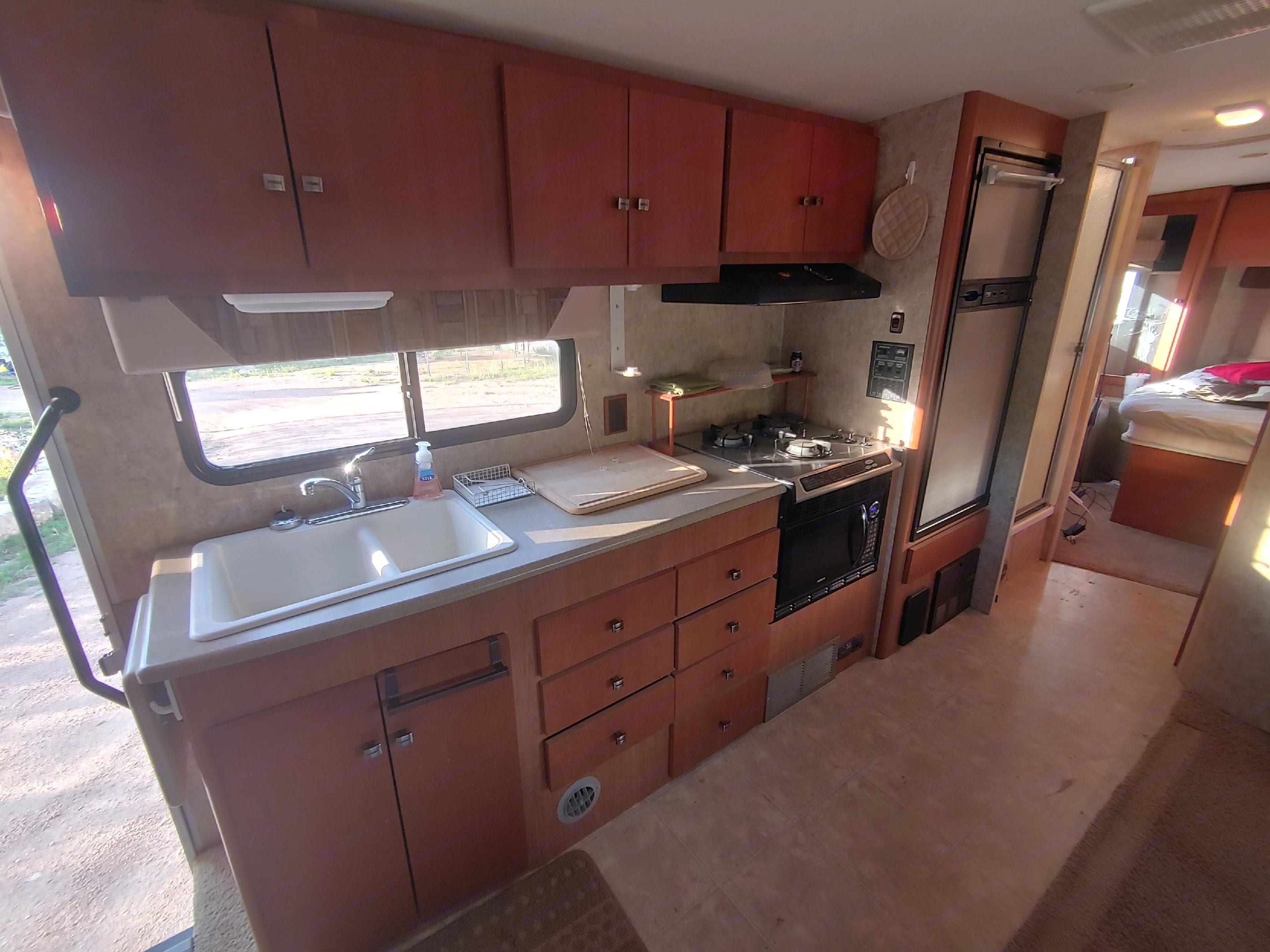 Kitchen area with fridge, 3 burner stove, combo convection/microwave oven. Plenty of space for your food prep.. Winnebago Outlook 2007